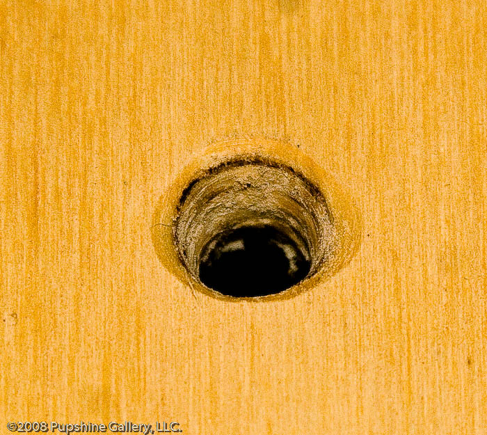 Finished hole in decking for cleat mounting bolt (close up)